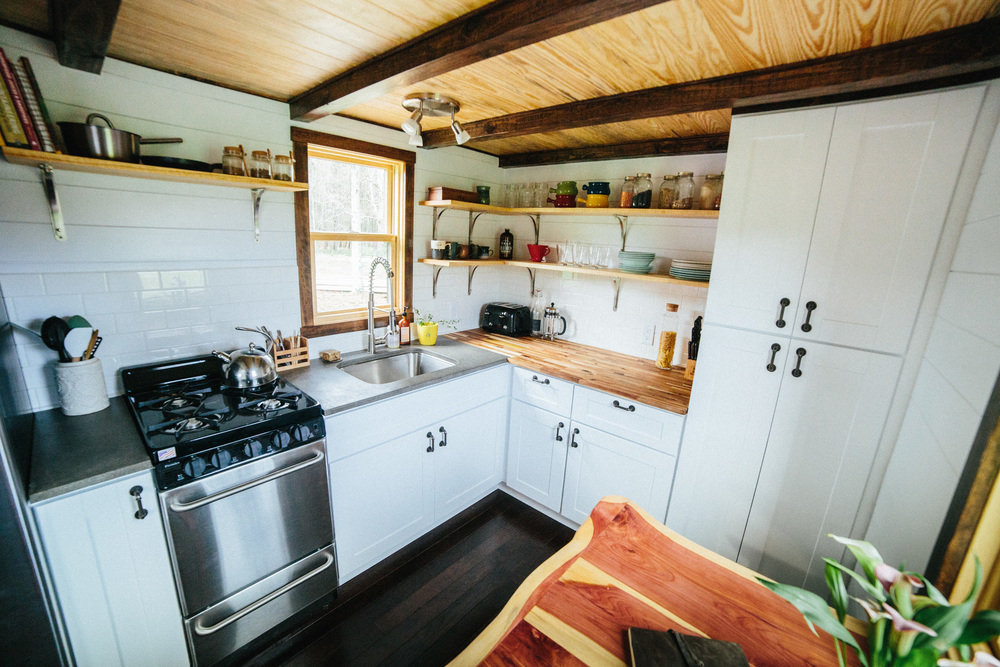 The Chimera by Wind River Tiny Homes. concrete and butcher block countertops, subway tile backsplash, open shelving, 20 in slide out pantry, live edge folding table and chairs.