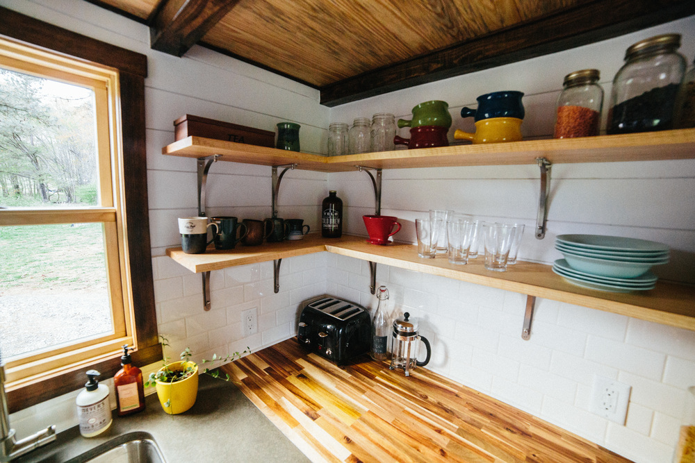 The Chimera by Wind River Tiny Homes. concrete and butcher block countertops, subway tile backsplash, open shelving.