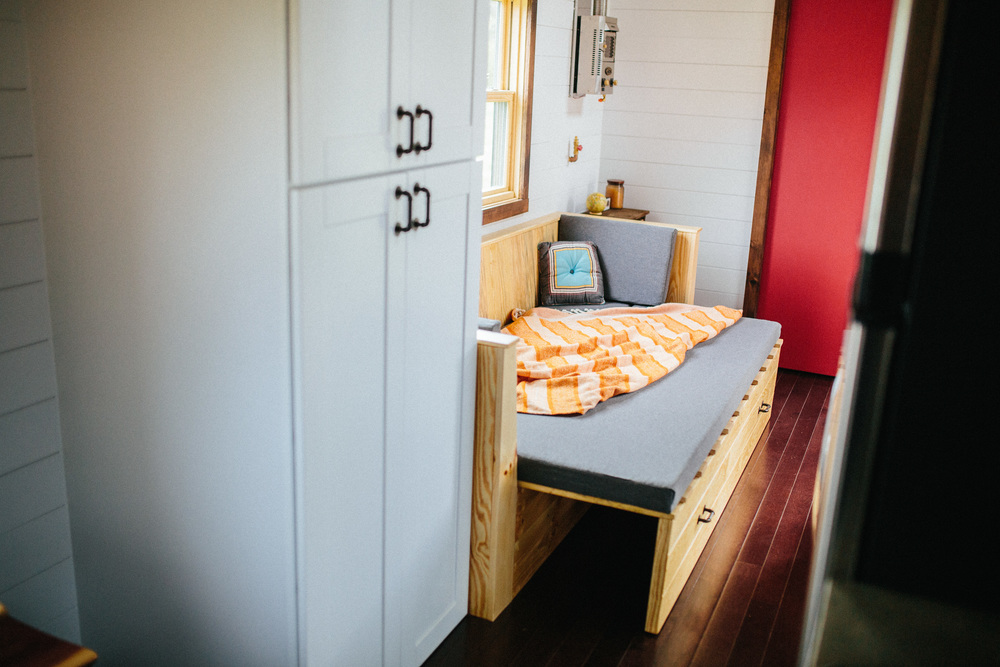 The Chimera by Wind River Tiny Homes. Clothing closet, custom built in couch that slides out for a bed and lifts for storage, bathroom at the end with storage loft.