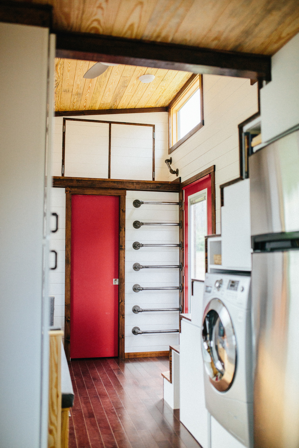 The Chimera by Wind River Tiny Homes. Custom built in couch that slides out for a bed and lifts for storage, bathroom at the end with storage loft, storage stairs.