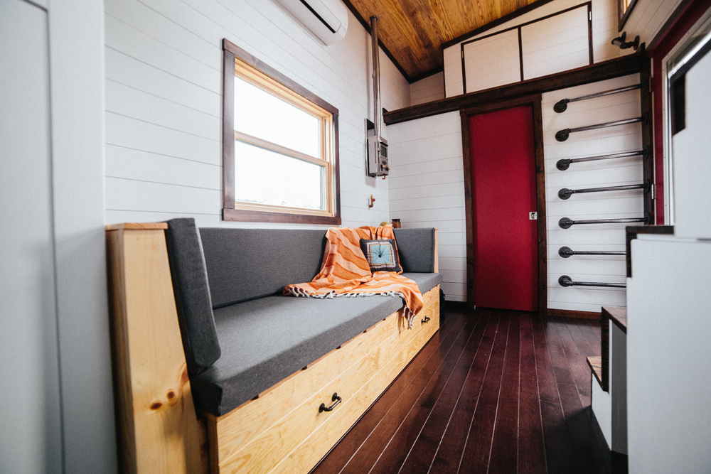 The Chimera by Wind River Tiny Homes. Custom built in couch that slides out for a bed and lifts for storage, bathroom at the end with storage loft, storage stairs