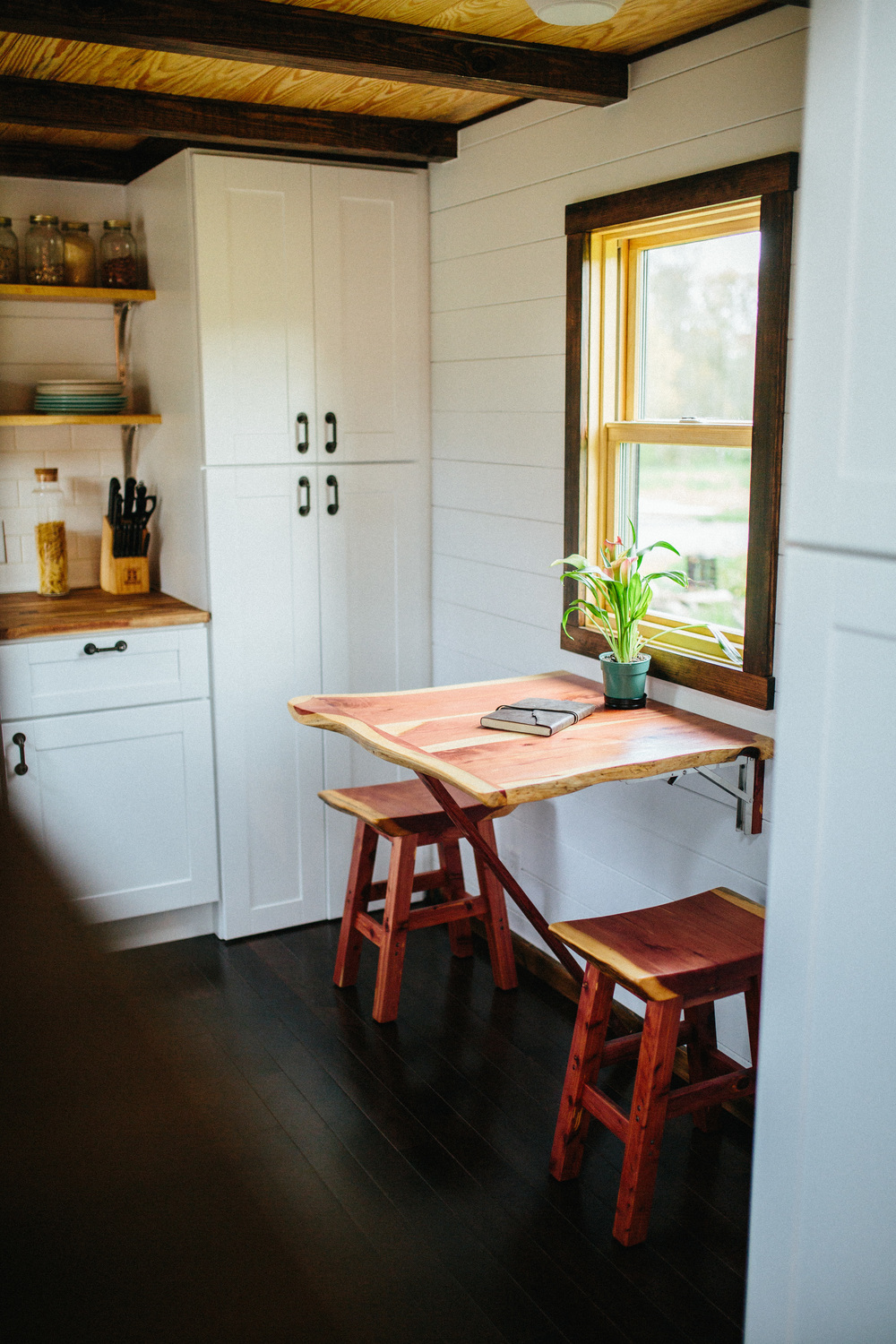 The Chimera by Wind River Tiny Homes. cedar live edge folding table and chairs.