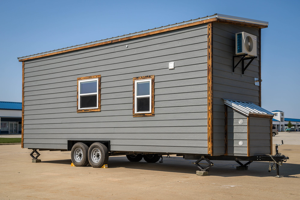 The Triton by Wind River Tiny Homes. Exterior back of home with storage box over hitch.