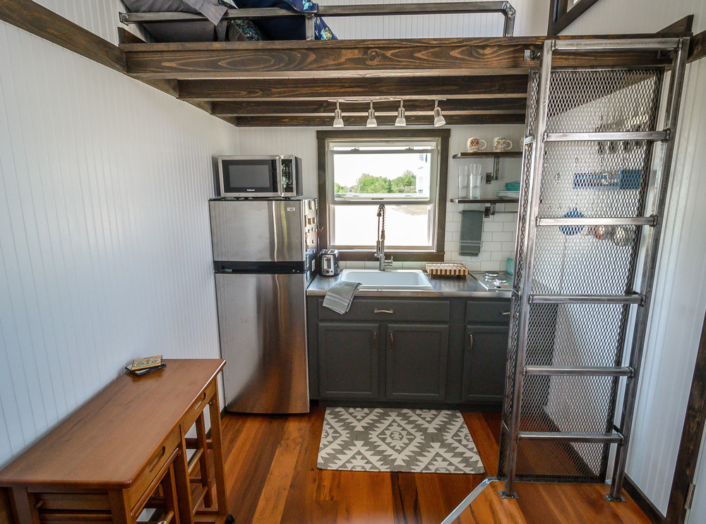 The Triton by Wind River Tiny Homes. Custom welded ladder with wire vertical storage leading up to storage loft. Custom welded shelving and stainless counters. White subway tile backsplash.