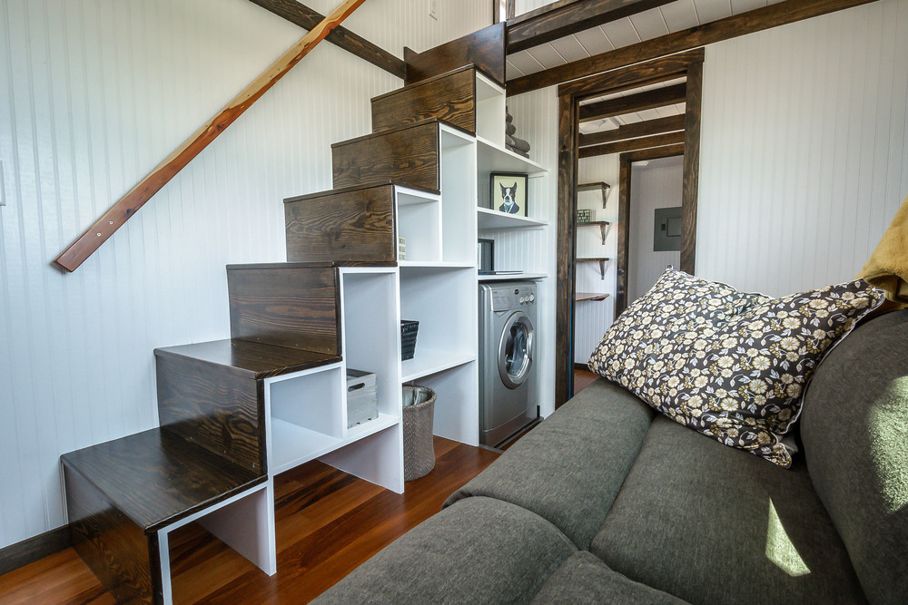The Triton by Wind River Tiny Homes. Custom storage stairs leading up to loft. Living space in the middle of home, with bathroom, office space, and walk in closet under loft.