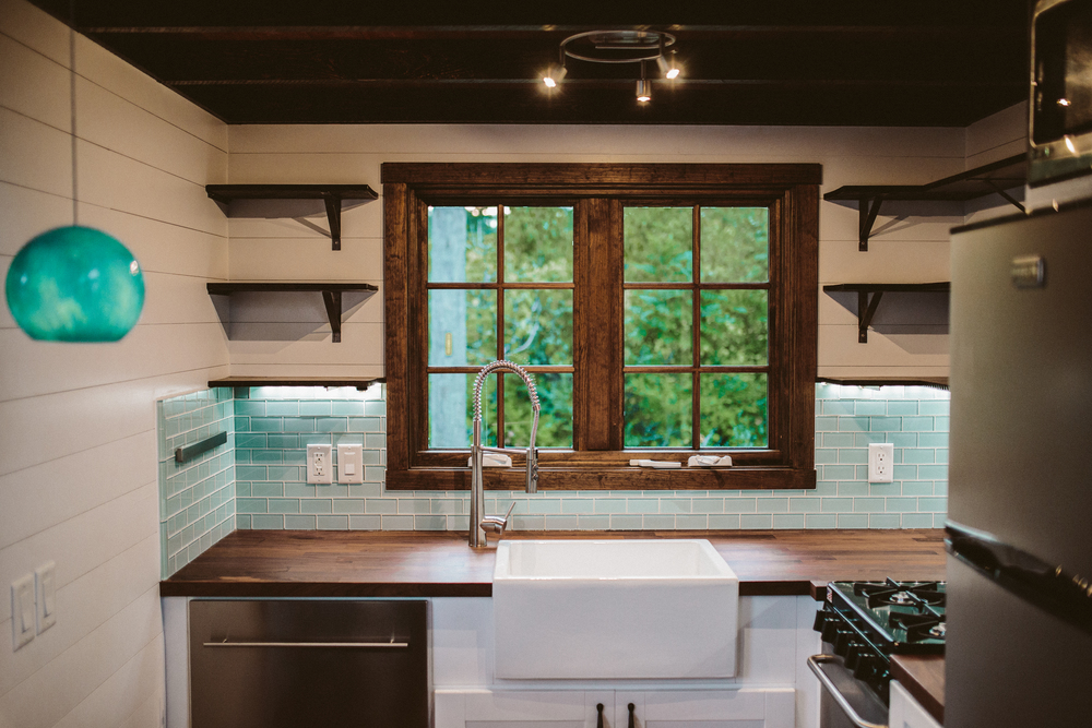 The Mayflower - Seaglass pendant, farmhouse sink, butcher block counters, custom welded open shelving, seaglass subway tile, oven, drawer dishwasher, and french casement window