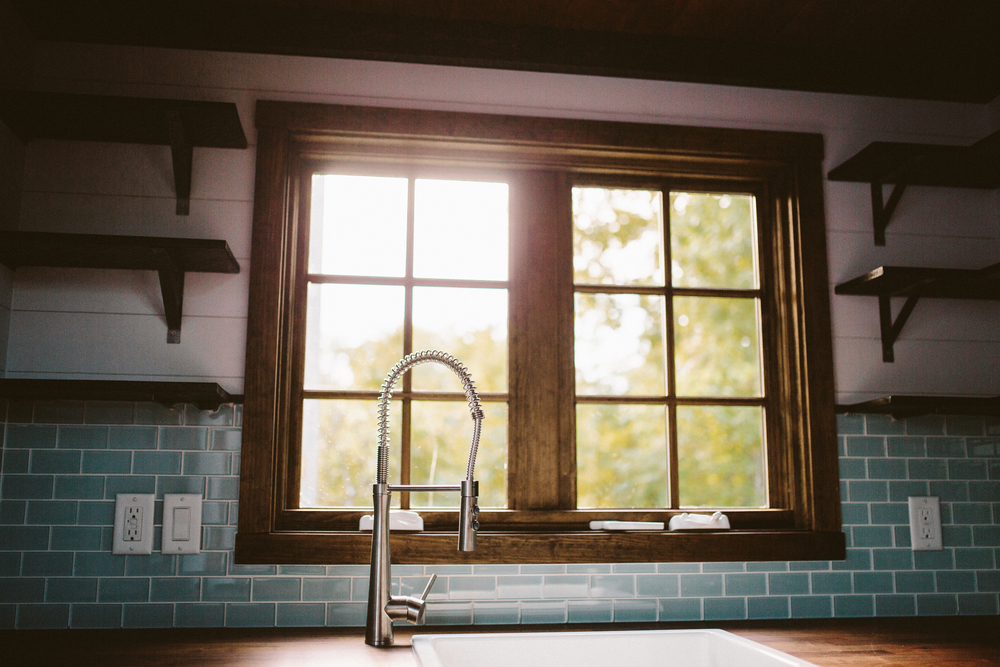 The Mayflower - Farmhouse sink, butcher block counters, custom welded open shelving, and seaglass subway tile