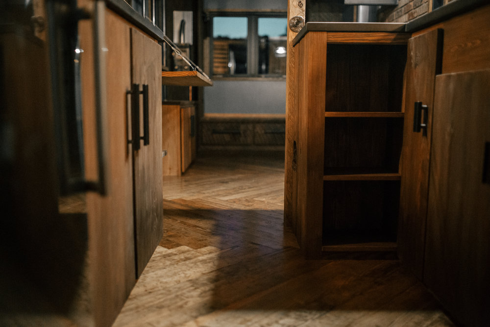 The Rook by Wind River Tiny Homes - Herringbone floors, built in custom cabinetry.