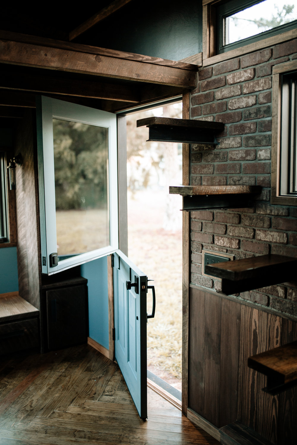 The Rook by Wind River Tiny Homes - Dutch door, floating rebar steps up to loft, herringbone floors, real brick veneer.