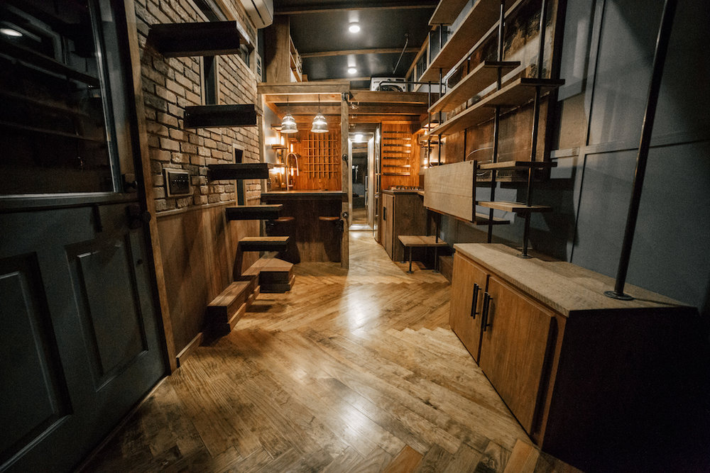 The Rook by Wind River Tiny Homes - Dutch door, custom welded bookshelf with fold down desk, floating rebar steps up to loft, herringbone floors.
