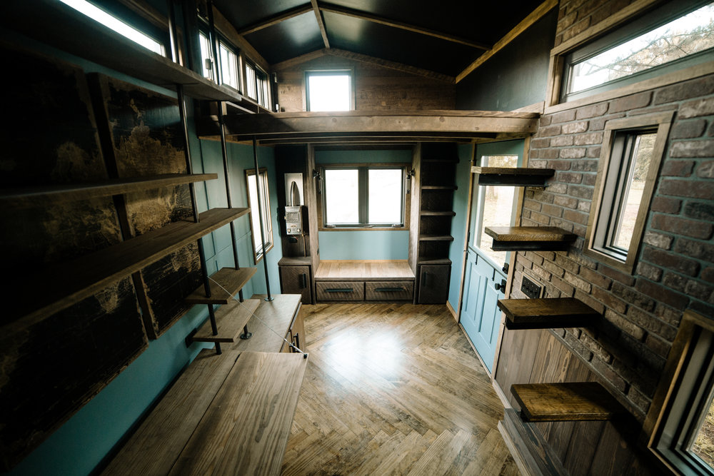 The Rook by Wind River Tiny Homes - Dutch door, custom welded bookshelf with fold down desk, floating rebar steps up to loft, herringbone floors, built in window seat couch.