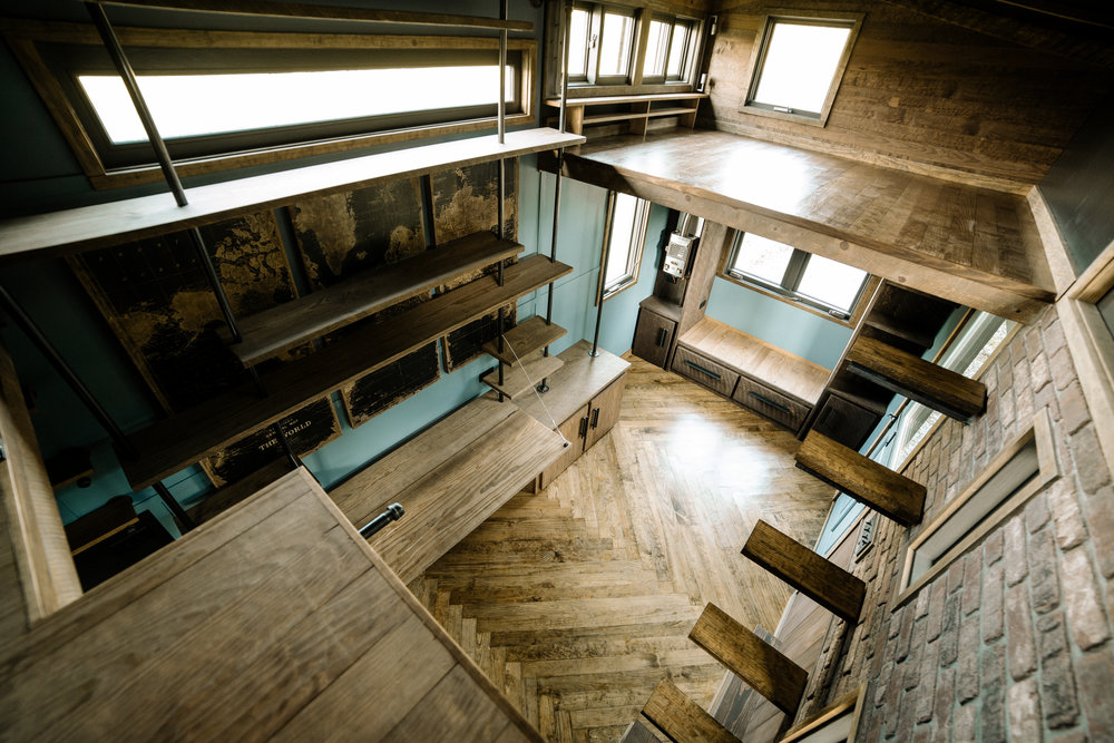 The Rook by Wind River Tiny Homes - Custom welded bookshelf with fold down desk, floating rebar steps up to loft, herringbone floors, built in window seat couch.