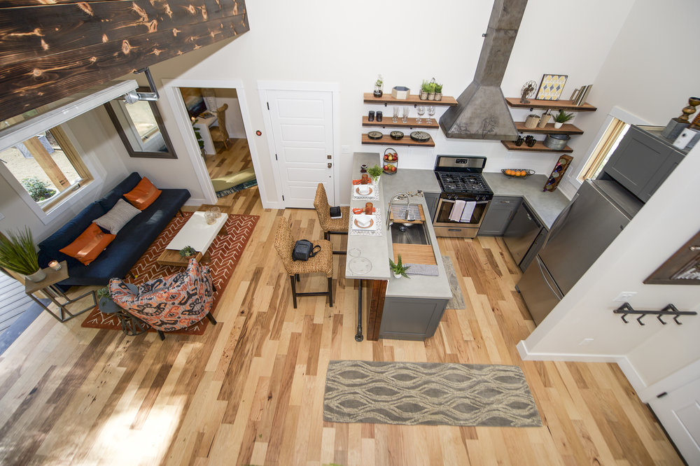 Urban Micro Home by Wind River Tiny Homes - glass garage door, stand up paddle board, rebar spindles, concrete countertops by Set In Stone, custom steel stove hood, contemporary design, rustic design