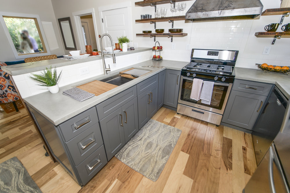 Urban Micro Home by Wind River Tiny Homes - concrete counter by Set In Stone, custom steel stove hood, shaker style cabinets, Galley Workstation 4 kitchen sink, reclaimed beam open shelving