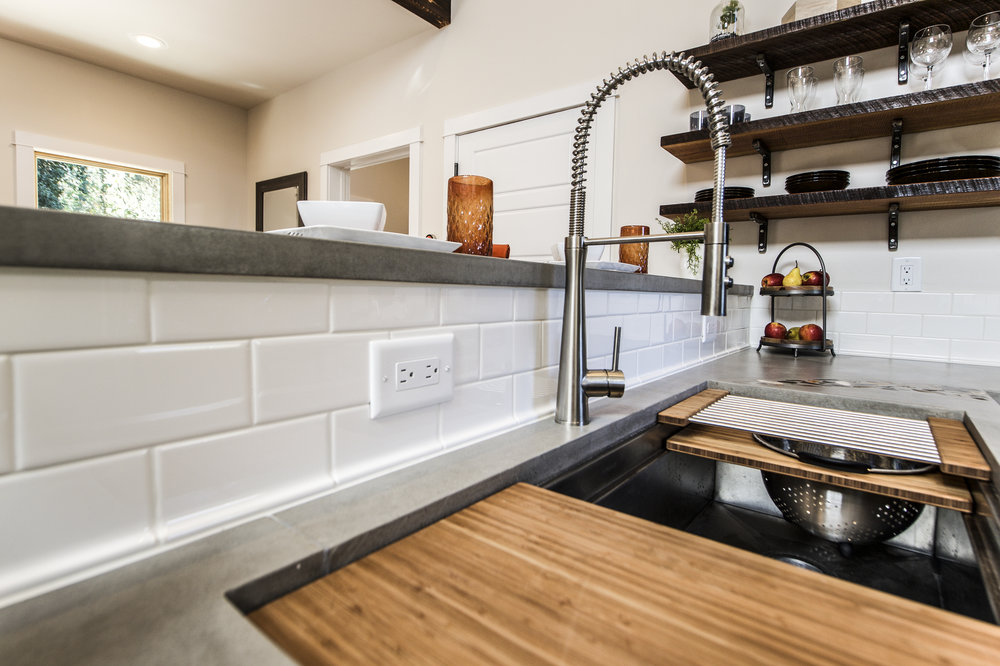 Urban Micro Home by Wind River Tiny Homes - concrete counter by Set In Stone, Galley Workstation 4 kitchen sink, subway tile backsplash, relaimed beam open shelving