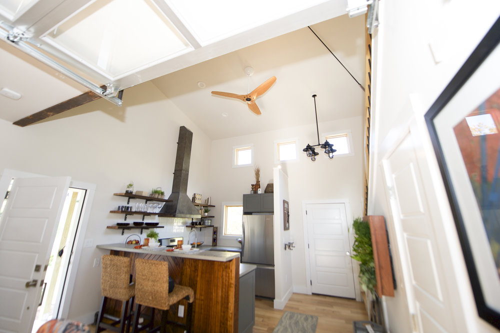 Urban Micro Home by Wind River Tiny Homes - glass garage door by Chattanooga Garage Door, Haiku bamboo fan by Big Ass Solutions, custom steel stove hood, reclaimed bar wood