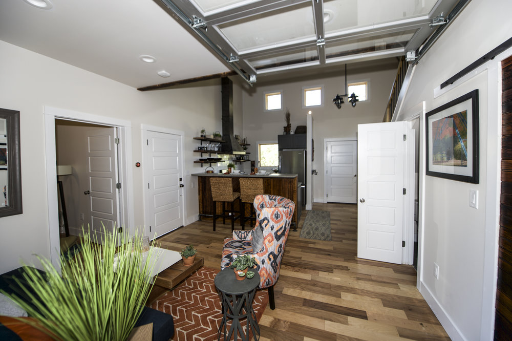 Urban Micro Home by Wind River Tiny Homes - glass garage door by Chattanooga Garage Door, sofa and coffee table by Smart Furniture, custom wood charred sliding barn door