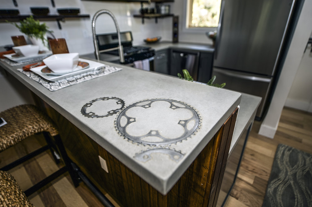 Urban Micro Home by Wind River Tiny Homes - concrete counter by Set In Stone, inlaid bike gears