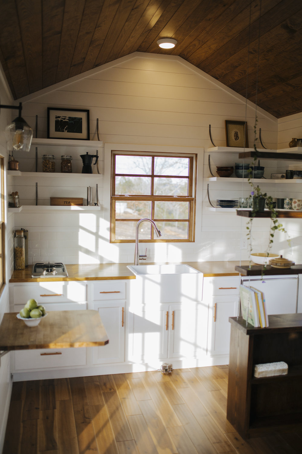 The Monocle by Wind River Tiny Homes - open shelving, fold down table, farmhouse sink, suspended cable shelving