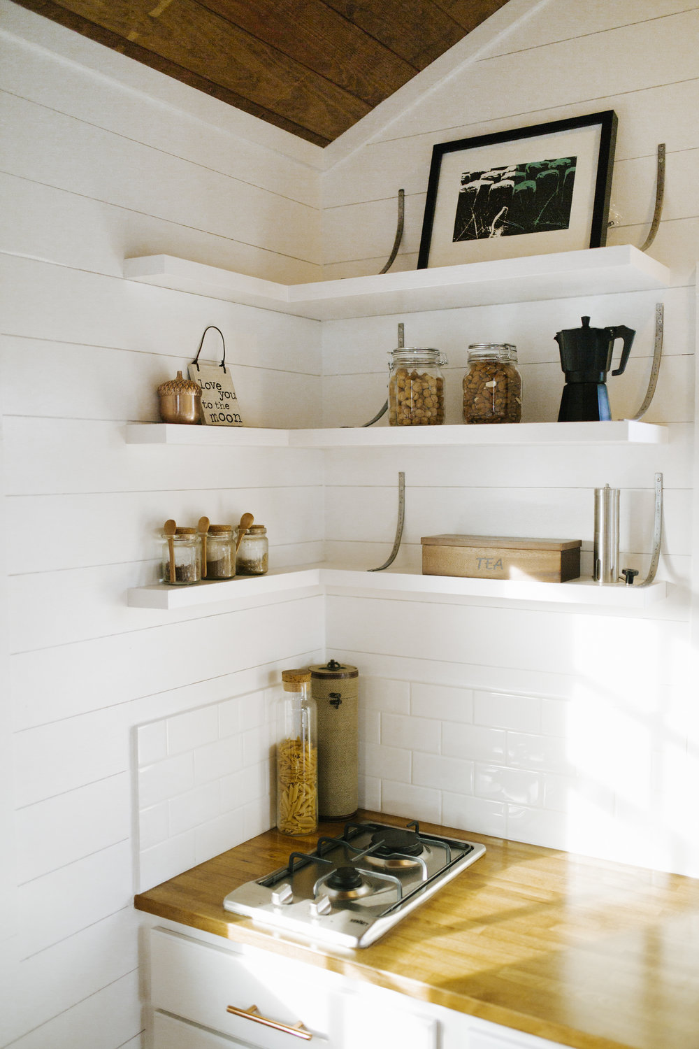 The Monocle by Wind River Tiny Homes - open shelving, custom steel brackets, propane 2 burner stove, butcher block countertops