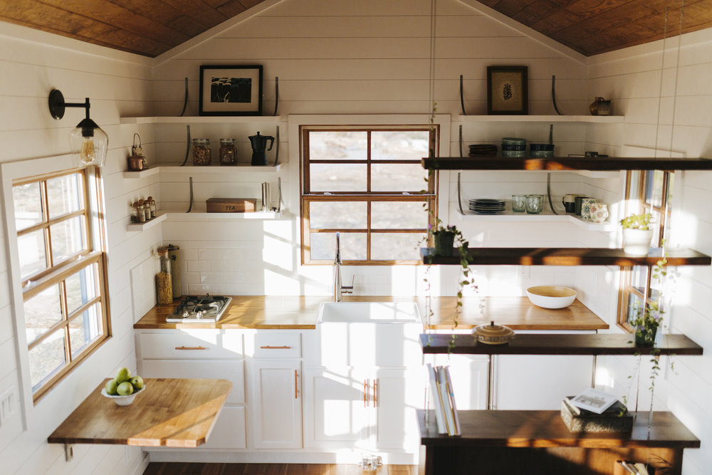The Monocle by Wind River Tiny Homes - open shelving, fold down table, farmhouse sink, butcher block countertops, suspended cable shelving