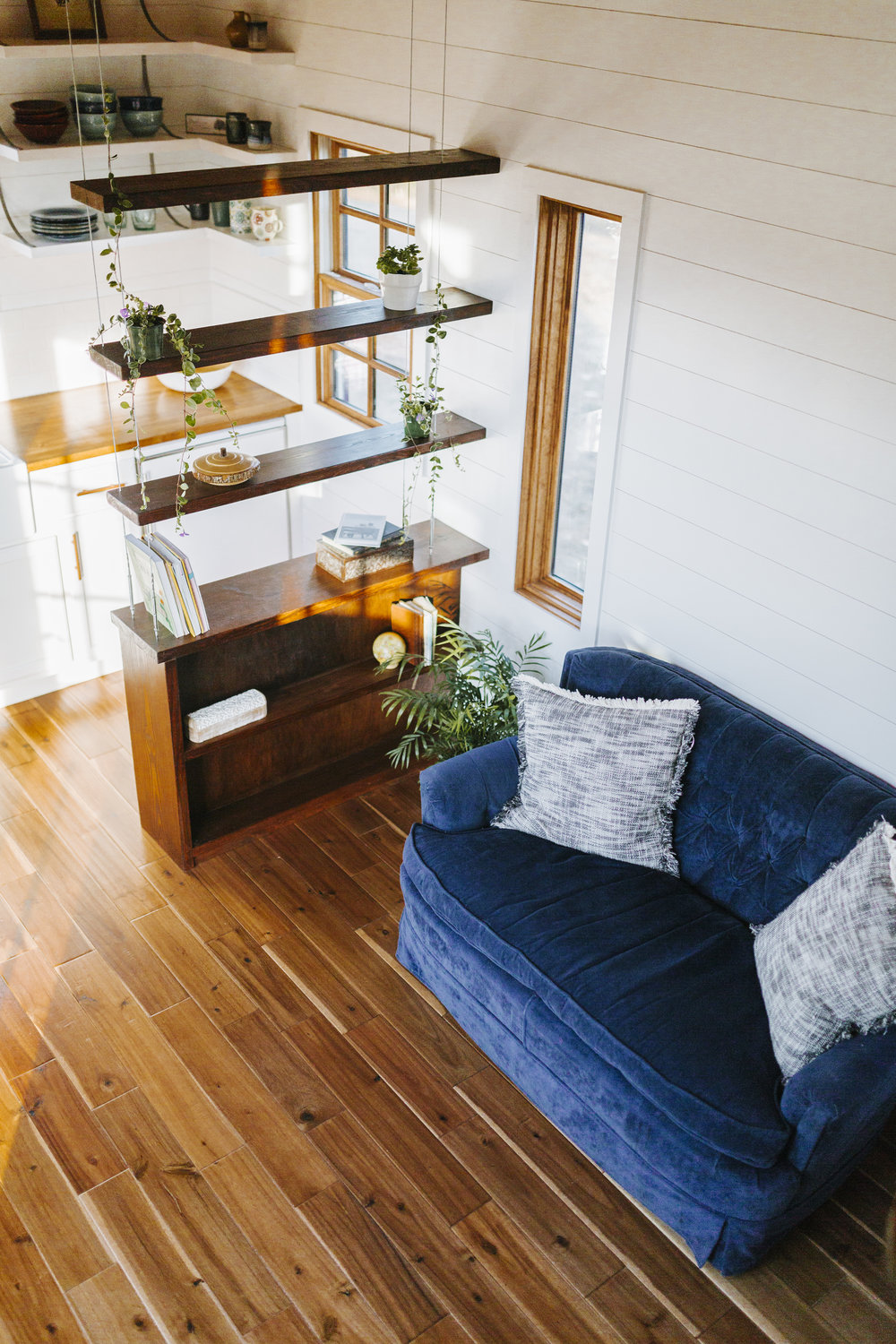 The Monocle by Wind River Tiny Homes - suspended cable shelving, wood clad windows, hardwood flooring, shiplap siding
