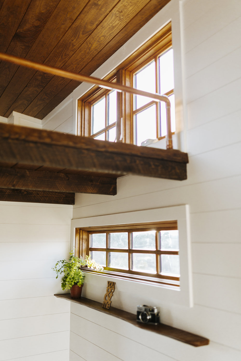 The Monocle by Wind River Tiny Homes - loft, wood clad windows, custom copper railing, live edge shelf