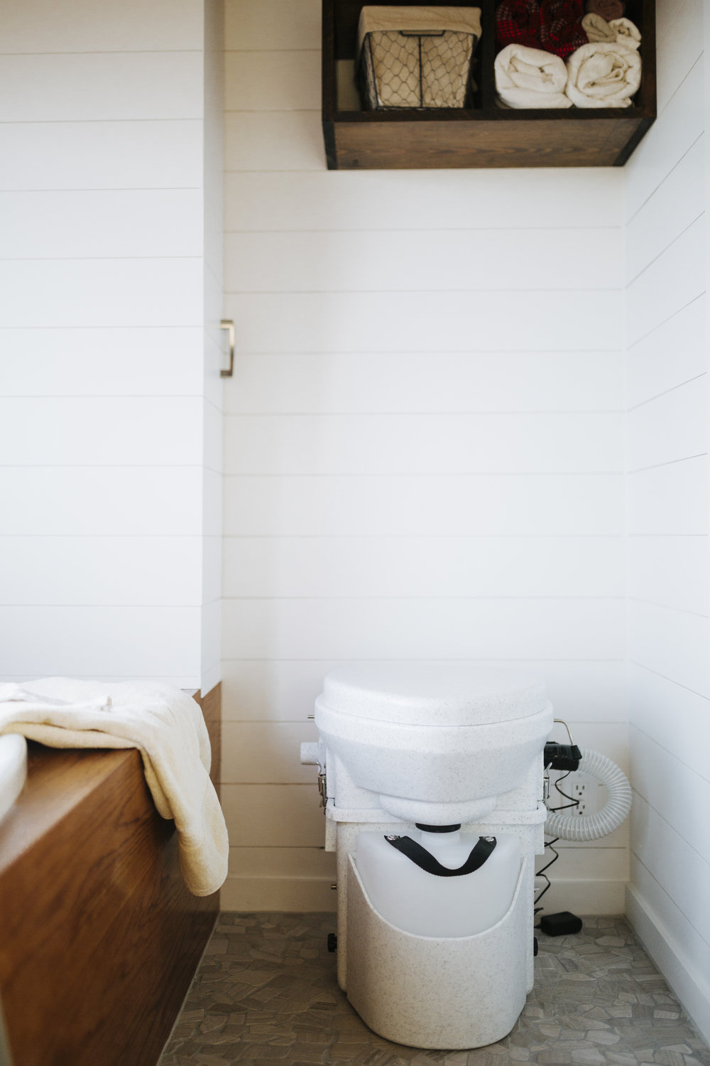 The Monocle by Wind River Tiny Homes - natures head composting toilet, pebble tile floor, wet bath, shiplap siding