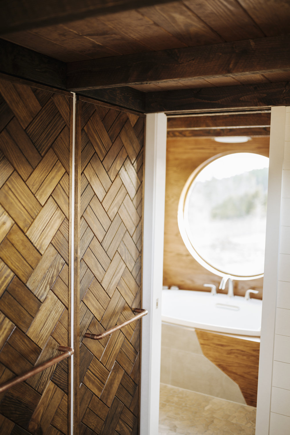 The Monocle by Wind River Tiny Homes - custom his/hers pull out closet, wood weave, copper pipe pulls, tile wet bath, bath tub