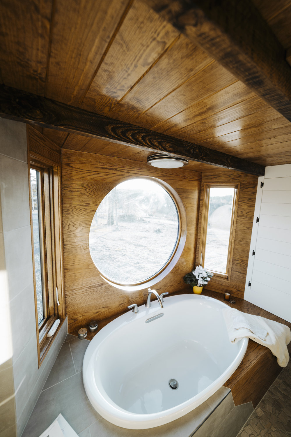 The Monocle by Wind River Tiny Homes - bath tub, wet bath, mixed tile and oak tub surround, pebble tile floor