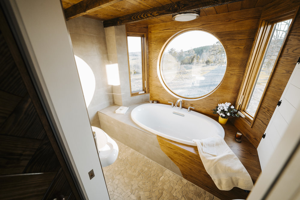 The Monocle by Wind River Tiny Homes - bath tub, wet bath, mixed tile and oak tub surround, pebble tile floor, floating sink