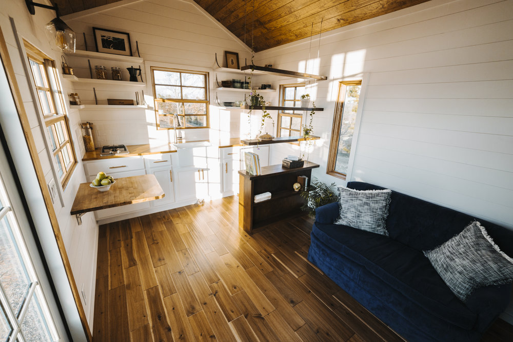 The Monocle by Wind River Tiny Homes - suspended cable shelf, fold down table, hardwood flooring, farmhouse sink