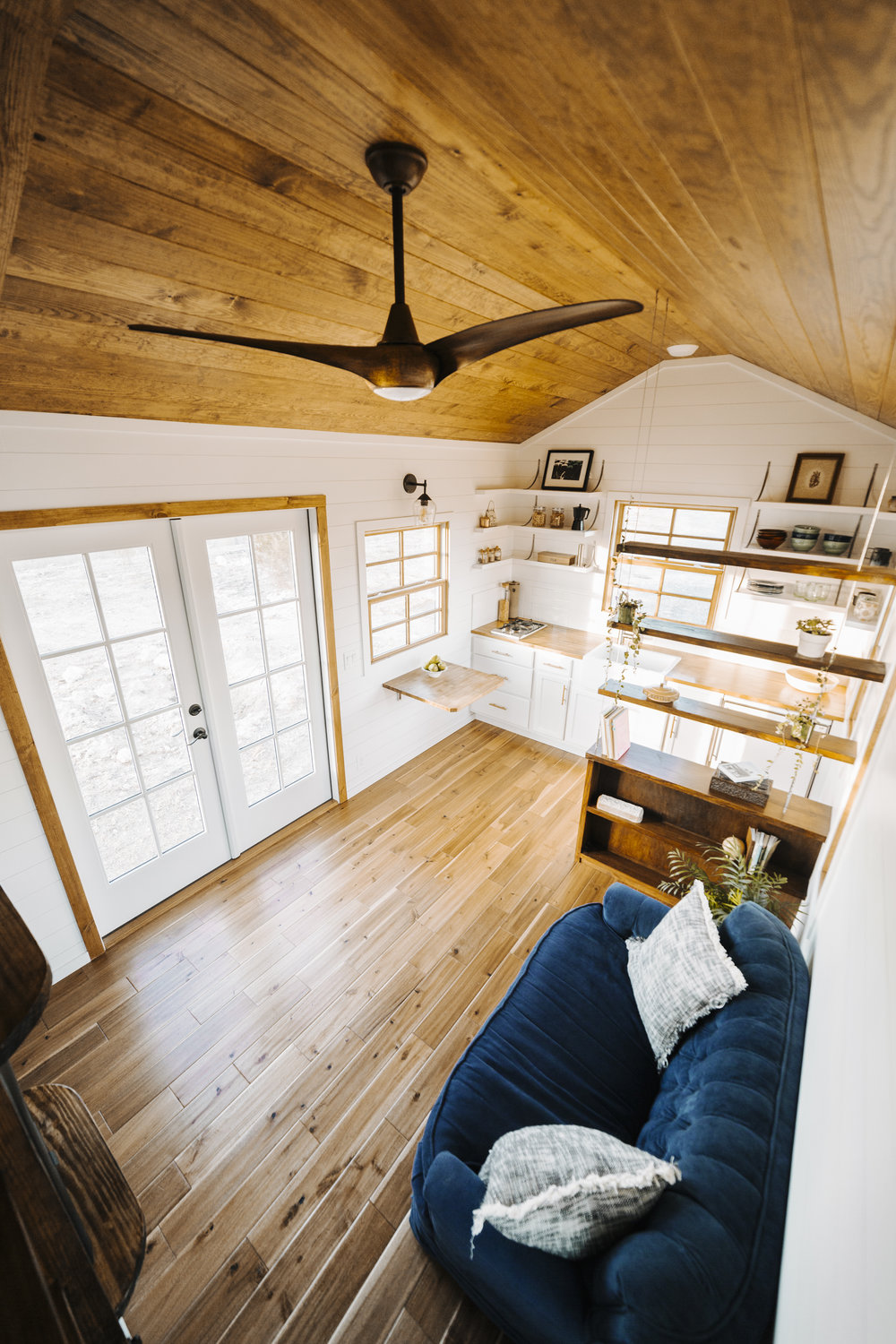 The Monocle by Wind River Tiny Homes - modern ceiling fan, hardwood flooring, loft, suspended cable shelving