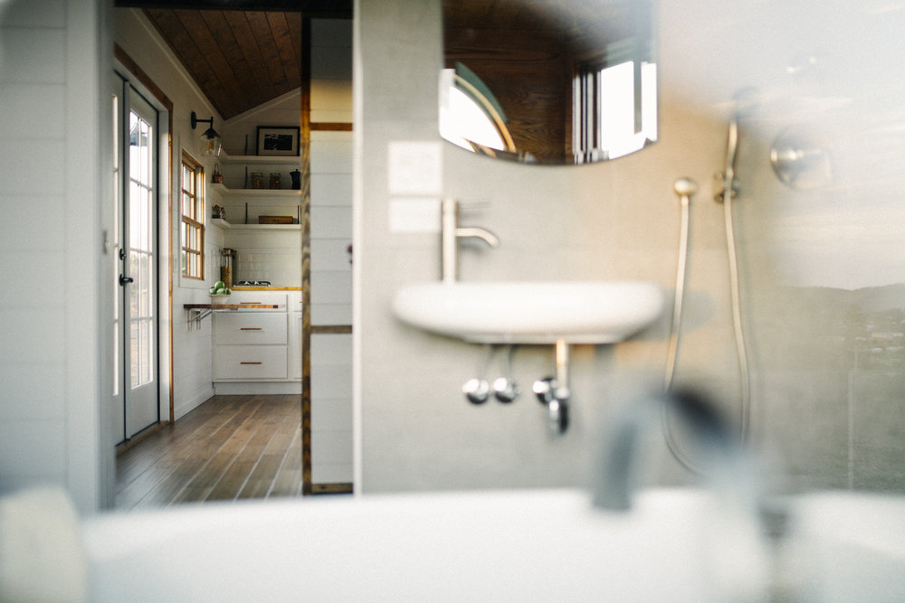 The Monocle by Wind River Tiny Homes - floating sink, recessed mirror cabinet, wet bath, rain shower head, hand held shower