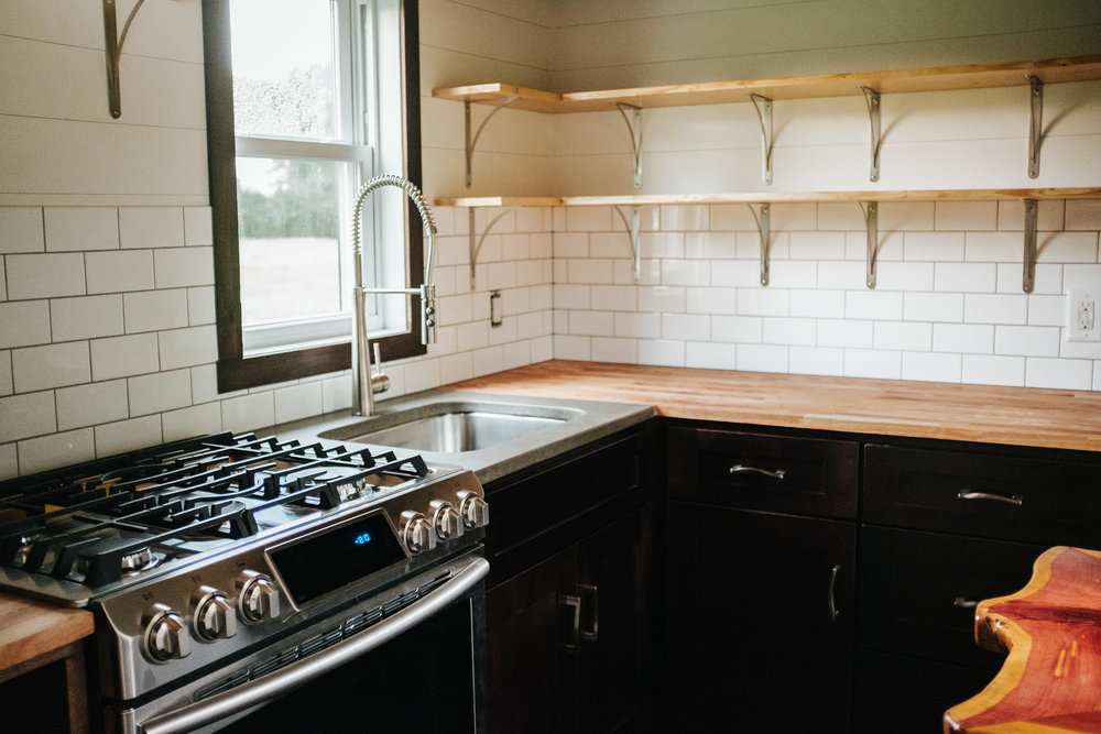 The Ironclad by Wind River Tiny Homes - concrete counter top, butcher block, subway tile, open shelving, propane range, shaker cabinets