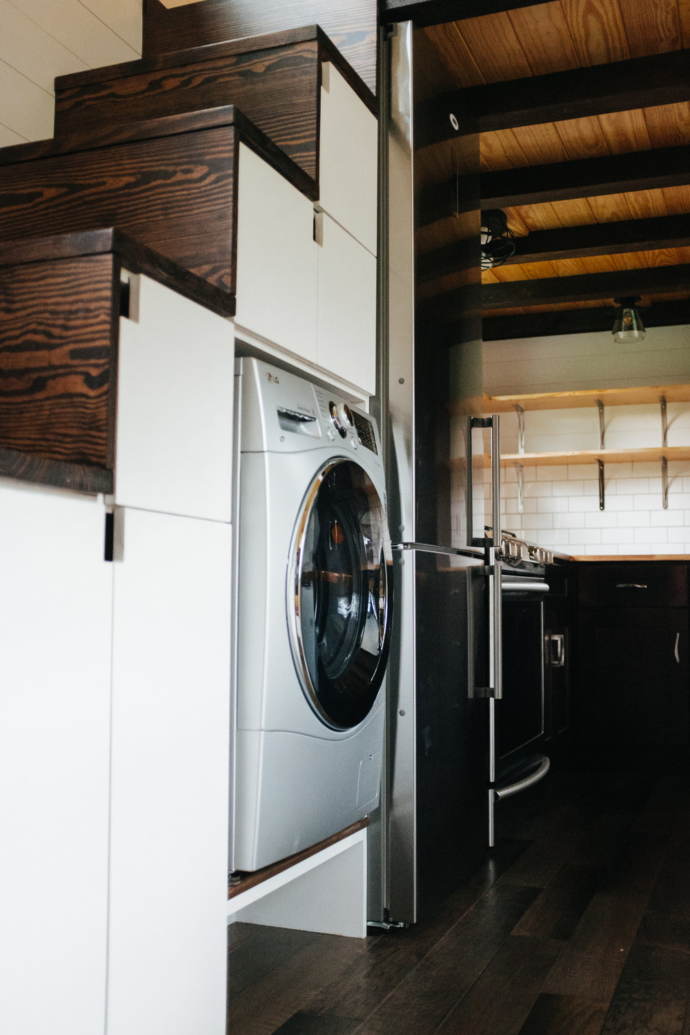 The Ironclad by Wind River Tiny Homes - washer dryer combo, custom storage stairs, ship lap
