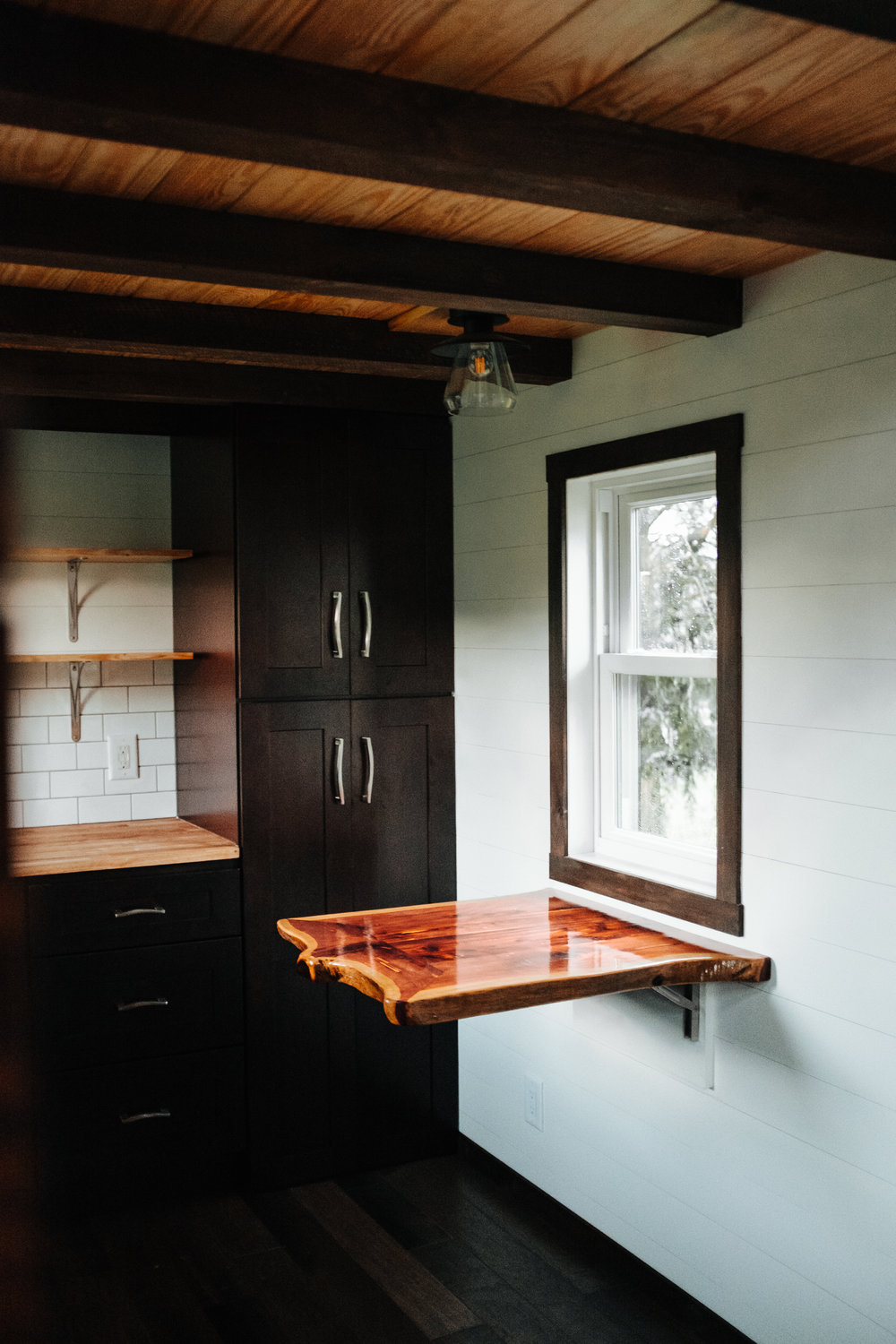 The Ironclad by Wind River Tiny Homes - shaker cabinets, cedar live edge table, ship lap