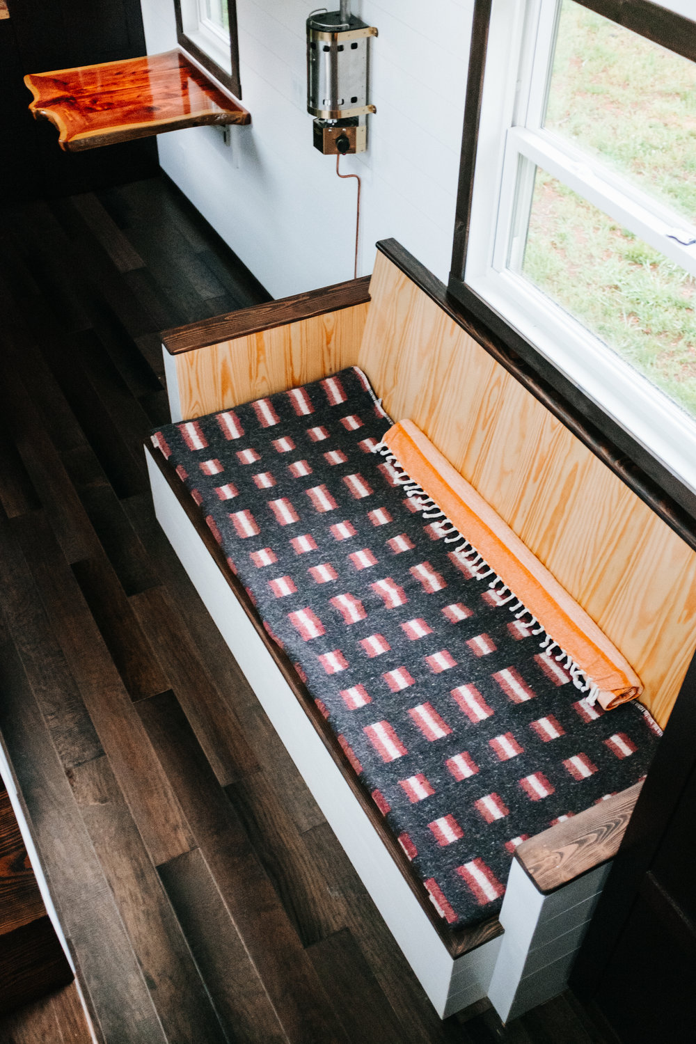 The Ironclad by Wind River Tiny Homes - custom storage couch, ship lap, live edge cedar table