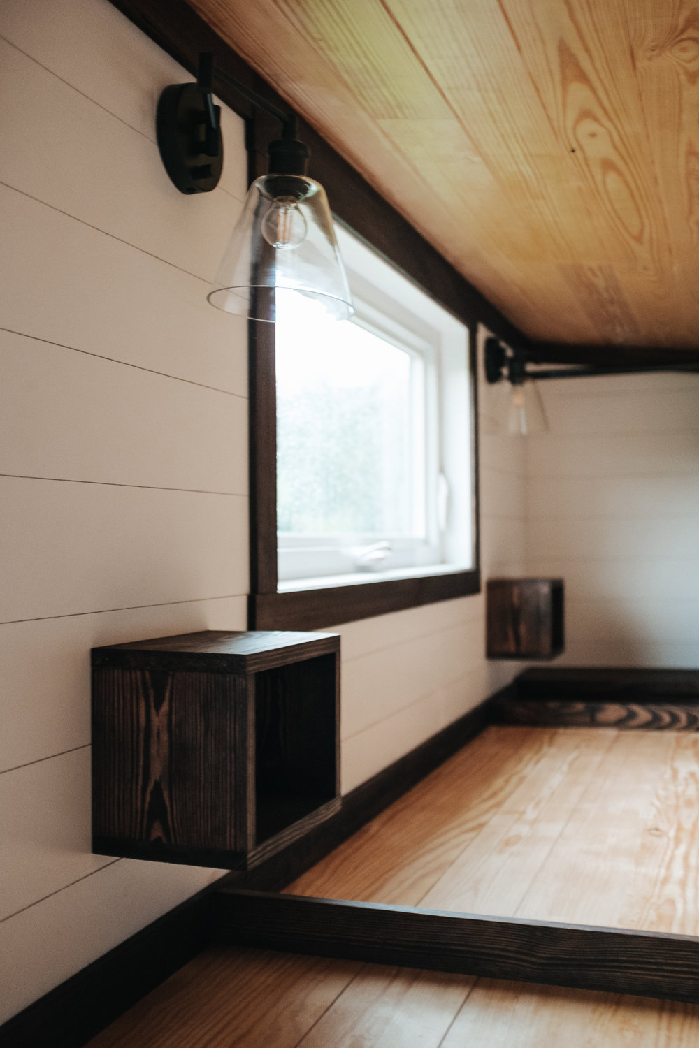 The Ironclad by Wind River Tiny Homes - natural pine ceiling, loft open storage, ship lap, industrial bed side light fixtures