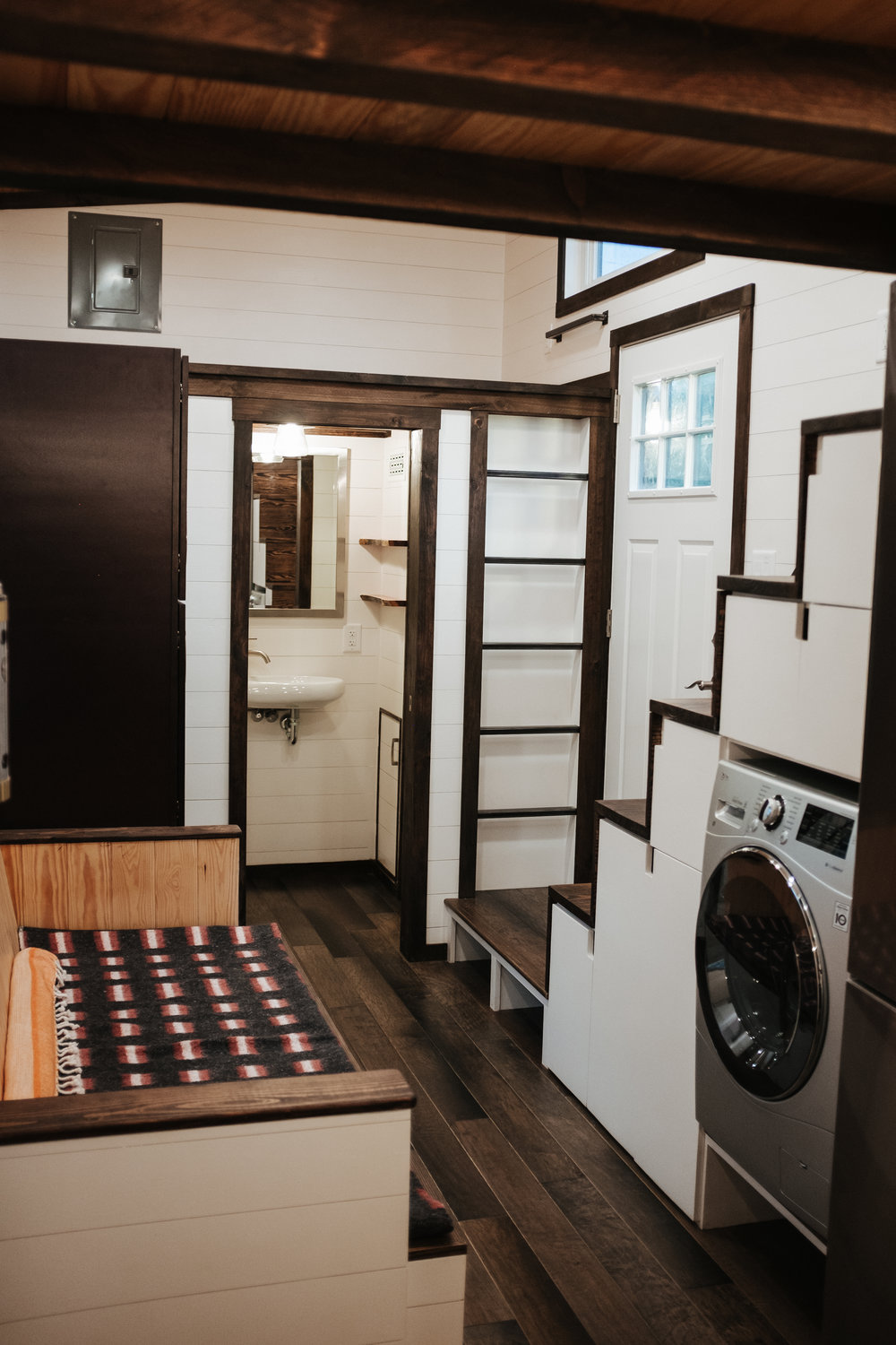 The Ironclad by Wind River Tiny Homes - washer dryer combo, custom storage stairs, storage couch, shaker style closet, built in steel ladder