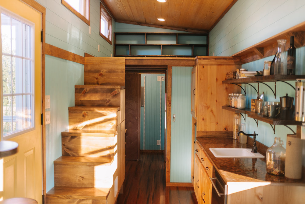 The Big Whimsy by Wind River Tiny Homes - bead board siding, built in storage stairs, Haiku ceiling fan, custom penny counter top, bamboo flooring, custom lily pad spiral stairs