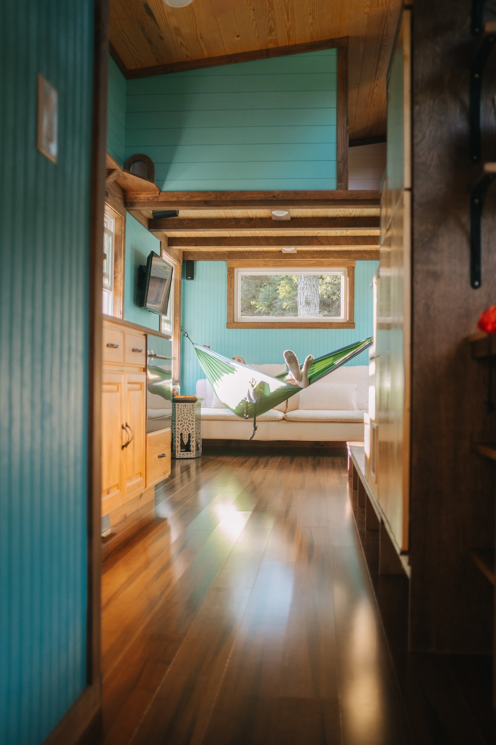The Big Whimsy by Wind River Tiny Homes - bead board siding, bamboo flooring, IKEA shelving, BOSE surround sound system, custom lily pad spiral stairs, hammock set-up