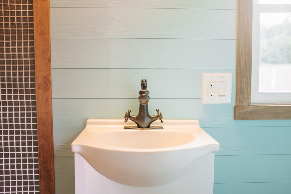 The Big Whimsy by Wind River Tiny Homes - bathroom vanity, oil rubbed bronze dragon faucet, tile shower