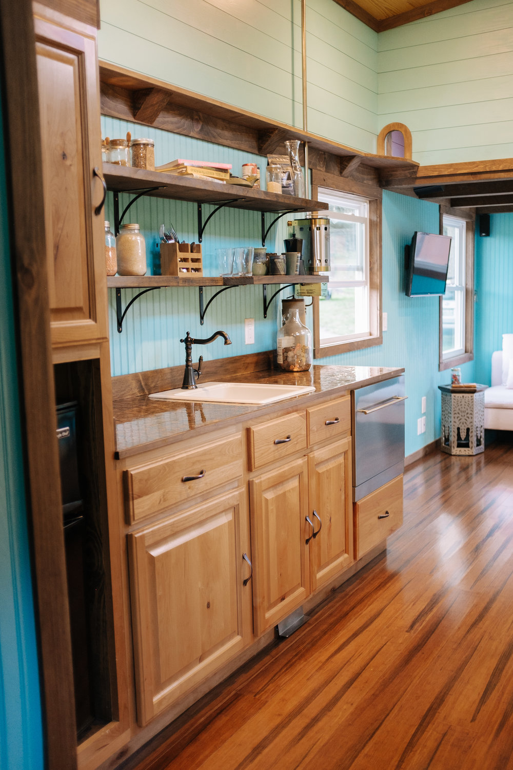 The Big Whimsy by Wind River Tiny Homes - compact dishwasher, open shelving, custom penny counter top, bamboo flooring, foot control kitchen faucet