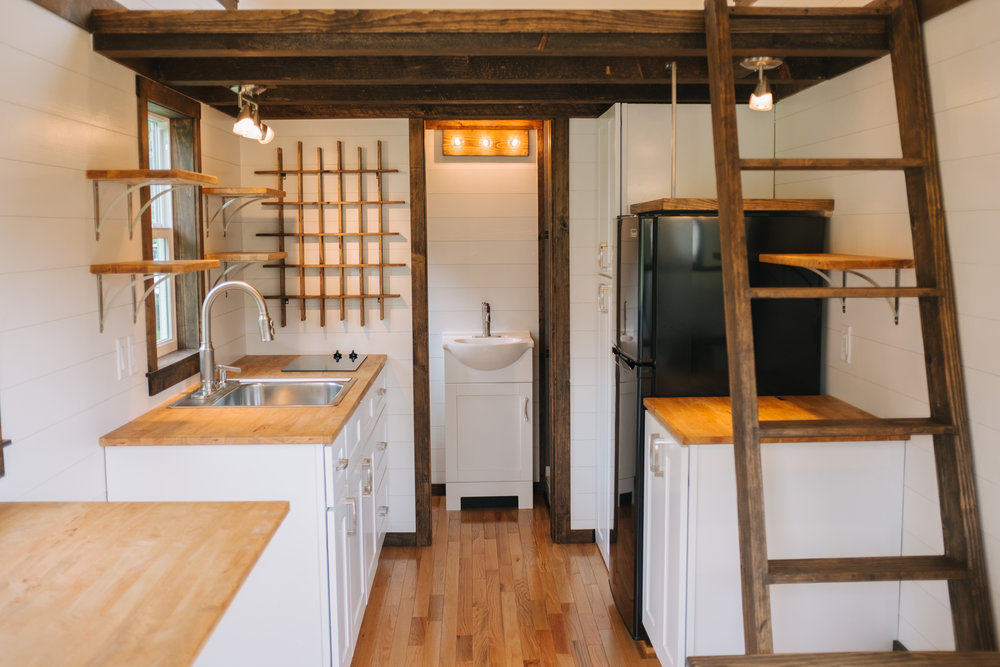 The Acadia by Wind River Tiny Homes - tiny house, butcher block counter top, Summit stove top, custom spice rack, loft ladder, fold down table