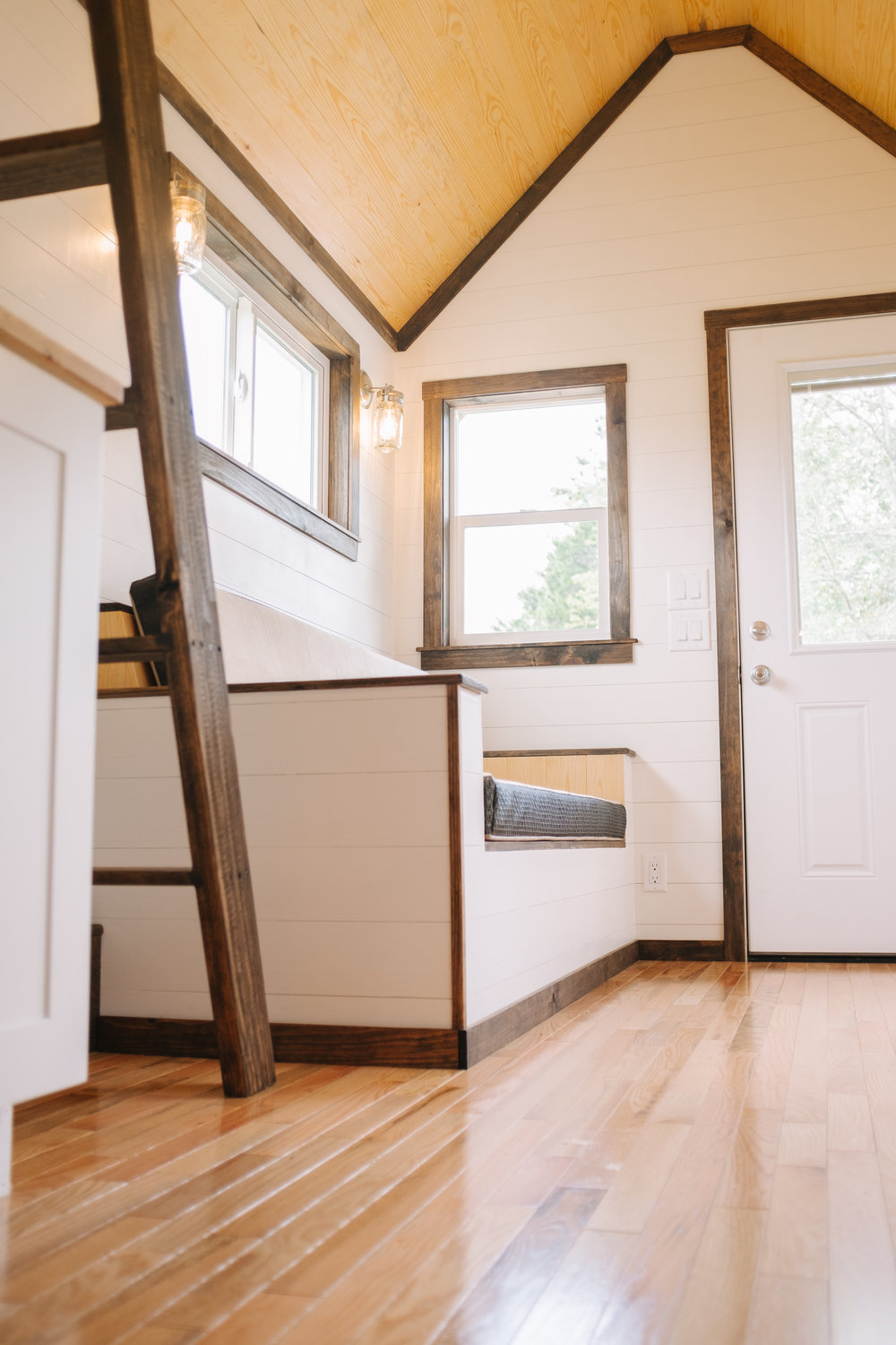 The Acadia by Wind River Tiny Homes - tiny house, ship lap, custom storage couch, oak hardwood flooring, loft ladder