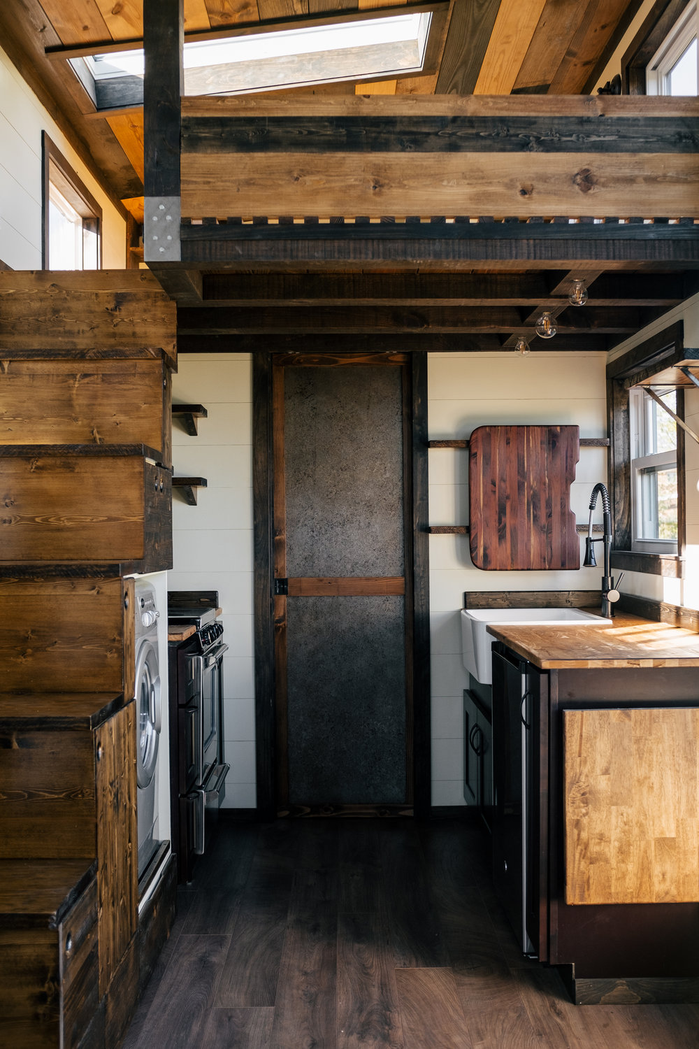 The Silhouette by Wind River Tiny Homes - shaker style cabinets, farmhouse sink, cedar sink cutting board, fold down table, storage stairs, patina steel pocket door