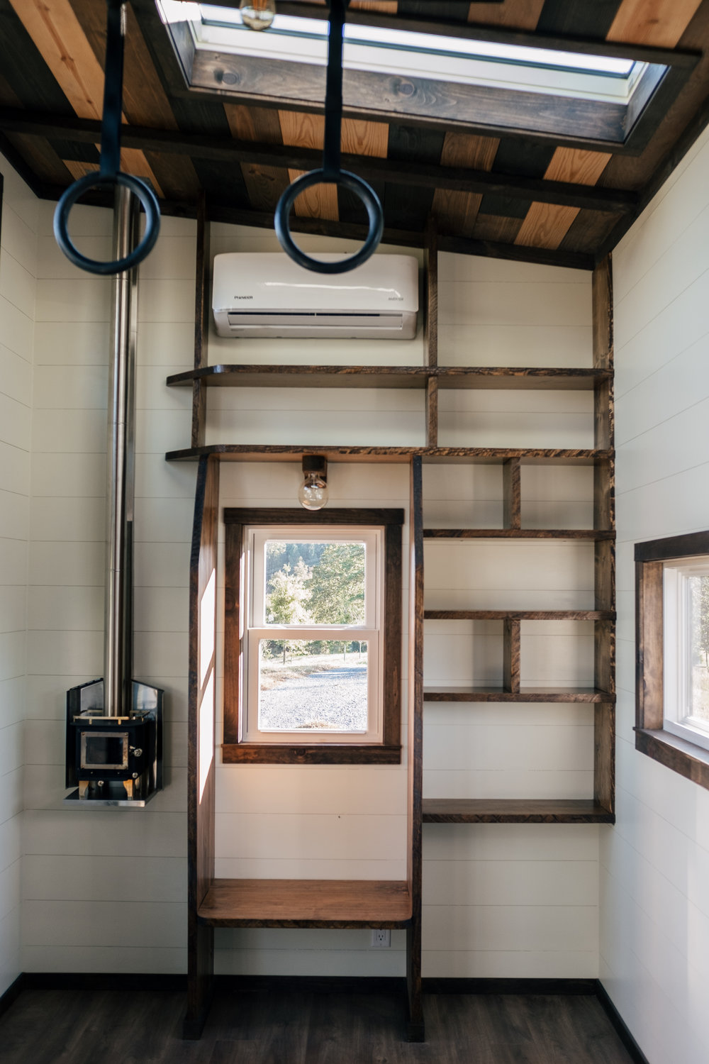 The Silhouette by Wind River Tiny Homes -  gym rings, integrated exercise floor, Cubic Mini wood stove, skylight