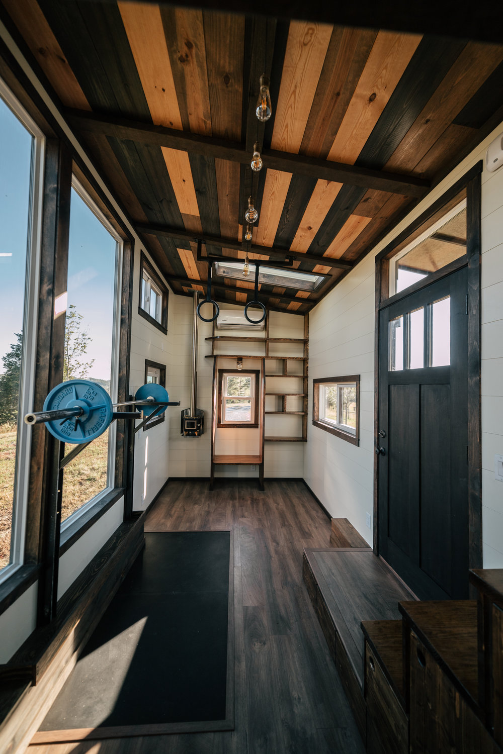 The Silhouette by Wind River Tiny Homes - custom olympic squat/bench rack, ship lap, integrated exercise floor, LED edison bulb light fixture, Cubic Mini wood stove
