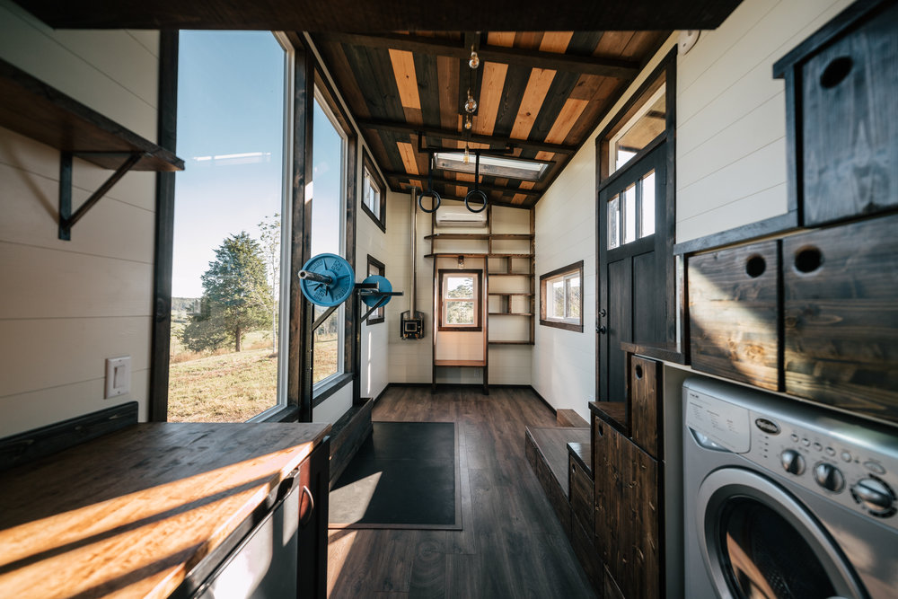The Silhouette by Wind River Tiny Homes - custom olympic squat/bench rack, gym rings, integrated exercise floor, Cubic Mini wood stove, washer dryer combo